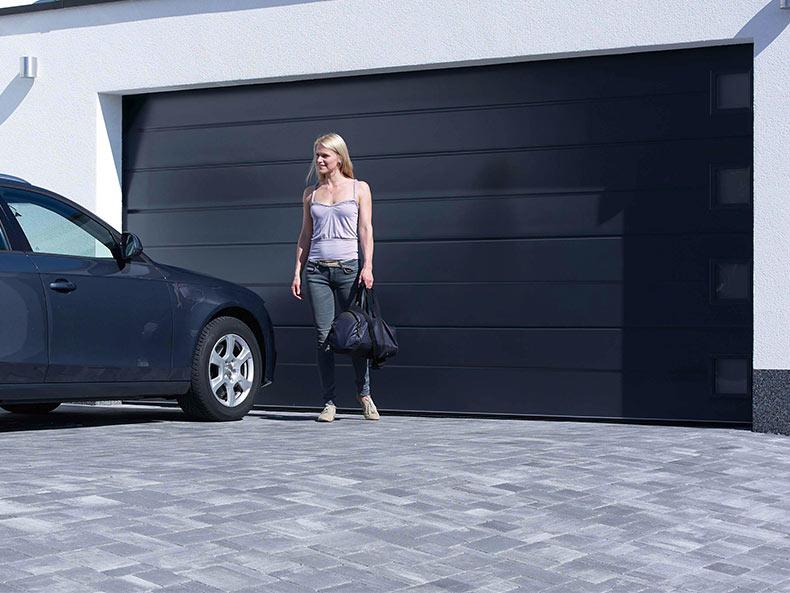 Dunkelgraues Garagen-Sektionaltor ohne Sicke mit einer Frau die zum Auto geht
