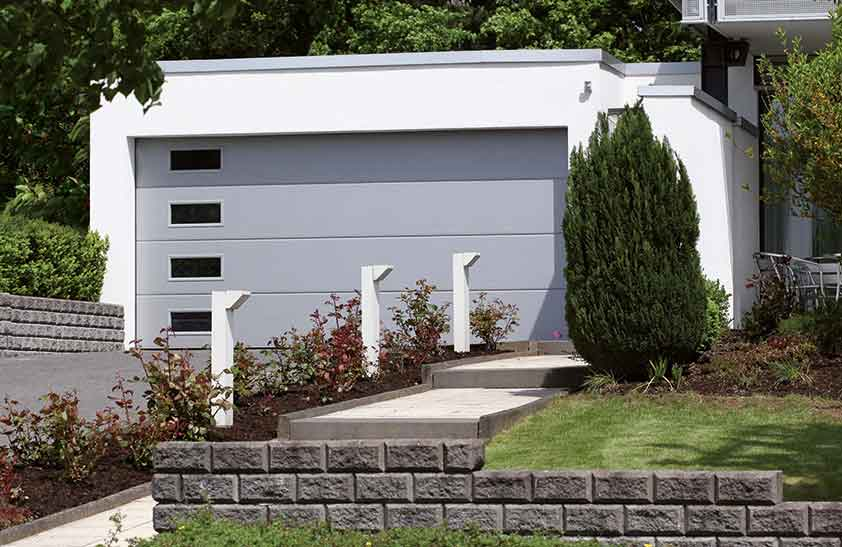Graues Garagen-Sektionaltor mit seitlichen Fensterelementen und einer Nebentür